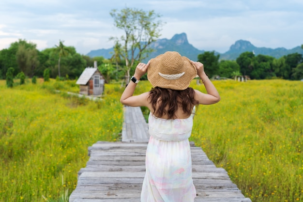Vrouw die hoed draagt en zich op houten brug met het gebied van de kosmosbloem bevindt