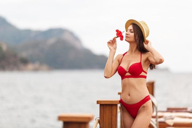 Vrouw die hoeden ruikende bloem draagt