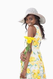 Vrouw die holdings gele bloemen bevindt zich