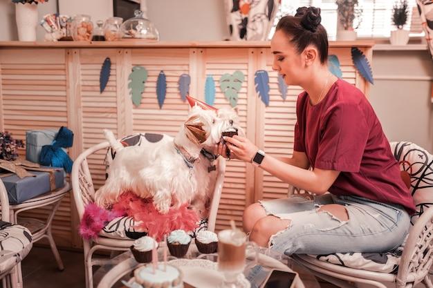 Vrouw die honden voedt. donkerharige jonge vrouw in spijkerbroek die haar honden cupcakes geeft