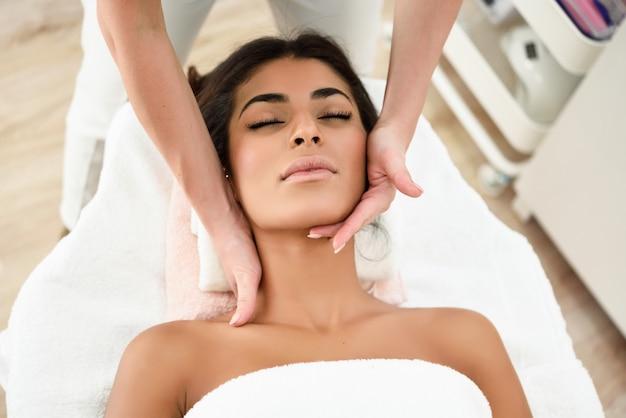 Vrouw die hoofdmassage in het centrum van kuuroordwellness ontvangt.