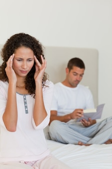 Vrouw die hoofdpijn heeft terwijl haar echtgenoot leest