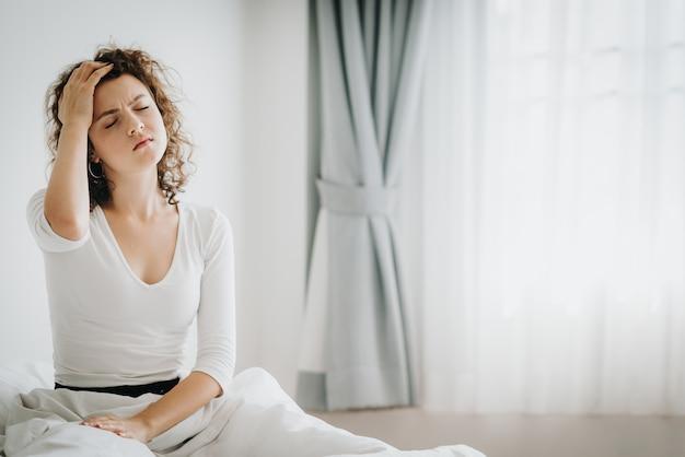 Vrouw die hoofdpijn voelt na het ontwaken in de ochtend