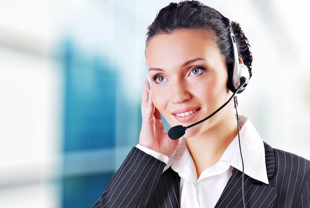 Vrouw die hoofdtelefoon in bureau draagt; kan receptioniste zijn