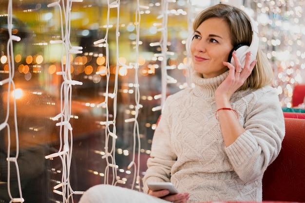 Vrouw die hoofdtelefoons draagt dichtbij kerstmislichten