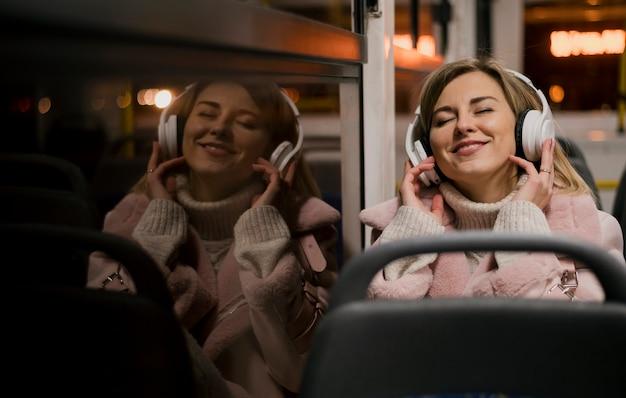 Vrouw die hoofdtelefoons draagt die in bus met gesloten ogen zitten