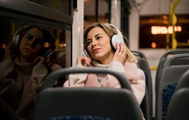 Vrouw die hoofdtelefoons draagt die in bus zitten