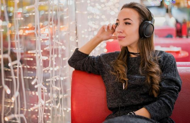 Vrouw die hoofdtelefoons draagt die kerstmislichten bekijken