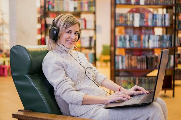 Vrouw die hoofdtelefoons draagt die vanaf laptop kijken