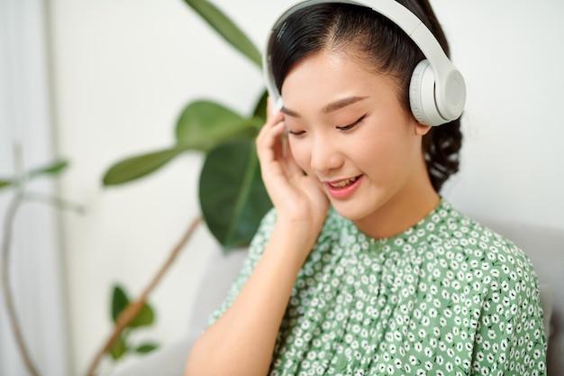 Vrouw die hoofdtelefoons draagt en een tablet in een woonkamer houdt