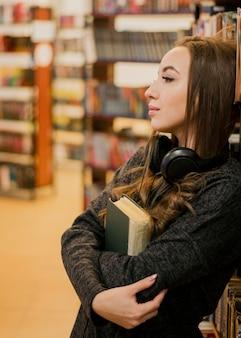 Vrouw die hoofdtelefoons draagt rond de hals die boek koestert