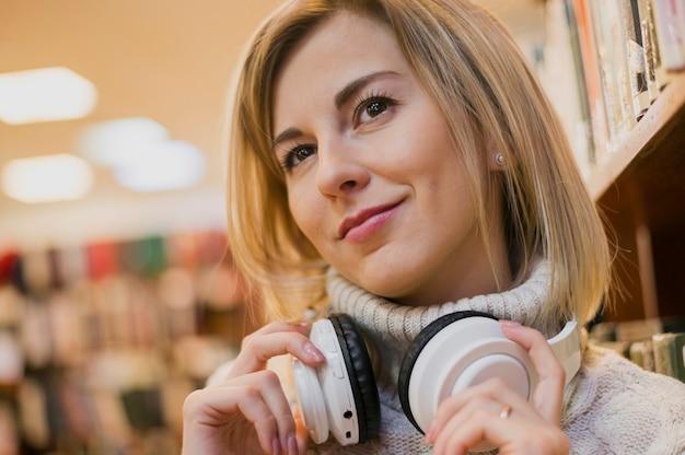 Vrouw die hoofdtelefoons draagt rond de hals in boekhandel