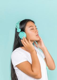 Vrouw die hoofdtelefoons met haar gesloten ogen draagt