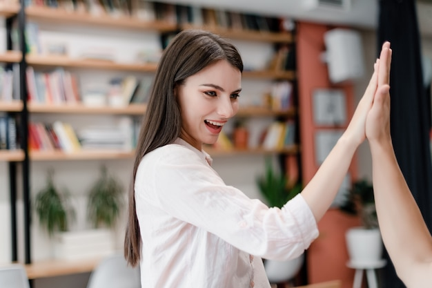 Vrouw die hoogte vijf in het bureau geeft