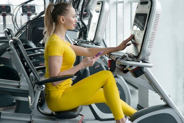 Vrouw die horizontale hometrainer in gymnastiek berijden