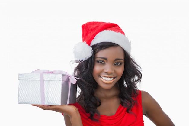 Vrouw die houdend een aanwezige kerstmis bevindt zich