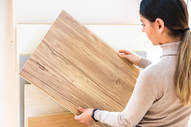 Vrouw die houten gelamineerde vloeren in winkel kiest. huis reparatie