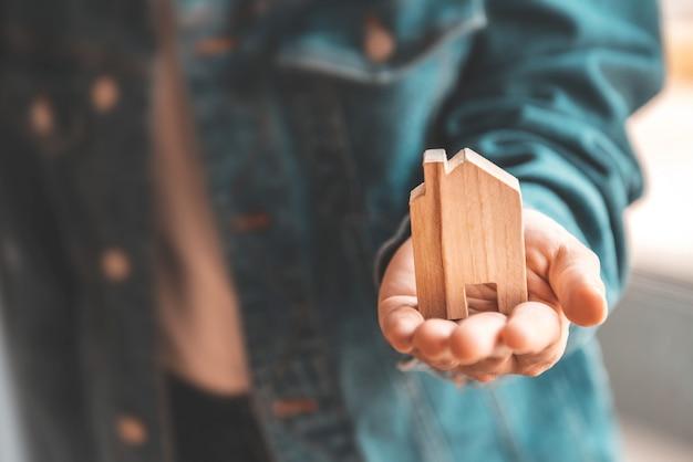 Vrouw die houten modelhuis in hand houdt