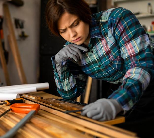 Vrouw die houten planken meet