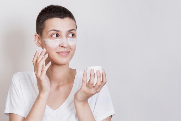 Vrouw die huidroom op haar gezicht gebruikt