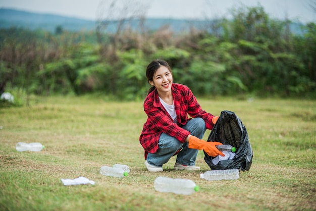 Vrouw die huisvuil in een zwarte zak verzamelt.