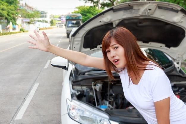 Vrouw die hulp na een autoanalyse zoeken, zich naast auto bevindt en een rit lift