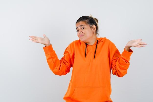 Vrouw die hulpeloos gebaar toont in oranje hoodie en verward kijkt