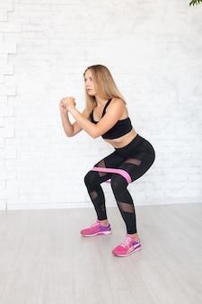 Vrouw die hurkzit met een elastiekje doet