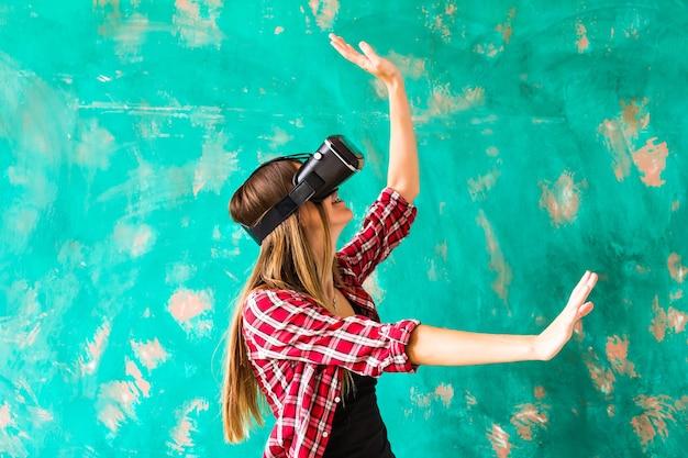 Vrouw die iets aanraakt met een virtual reality-headsetbril.