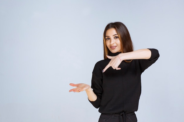 Vrouw die iets in haar hand toont. Gratis Foto
