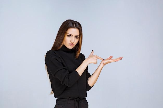 Vrouw die iets in haar hand toont.