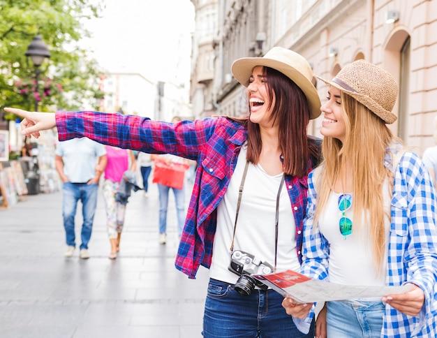 Vrouw die iets toont aan haar gelukkige vrouwelijke vrienden die kaart houden