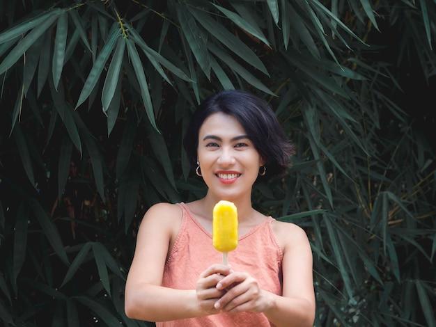 Vrouw die ijslollys eet. fijne mooie aziatische vrouw die een casual roze tanktop draagt met een gele ijslolly op een groene tropische palmbladerenachtergrond, buiten glimlachend vrouwtje genieten van ijslolly in de zomer.