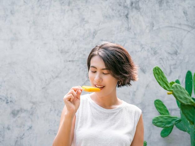 Vrouw die ijslollys eet. fijne mooie aziatische vrouw met kort haar, gekleed in een wit mouwloos shirt met gele ijslolly, buitenshuis. glimlachend vrouwtje genieten van ijslolly in de zomer.