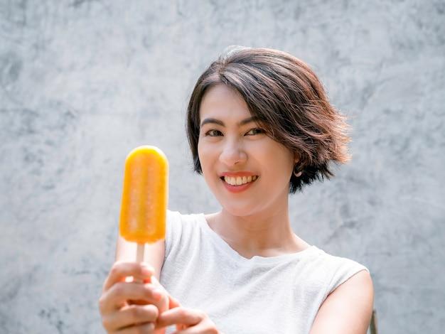 Vrouw die ijslollys eet. fijne mooie aziatische vrouw met kort haar in een casual wit mouwloos shirt met een gele ijslolly op een grijze betonnen muurachtergrond in de zomer.