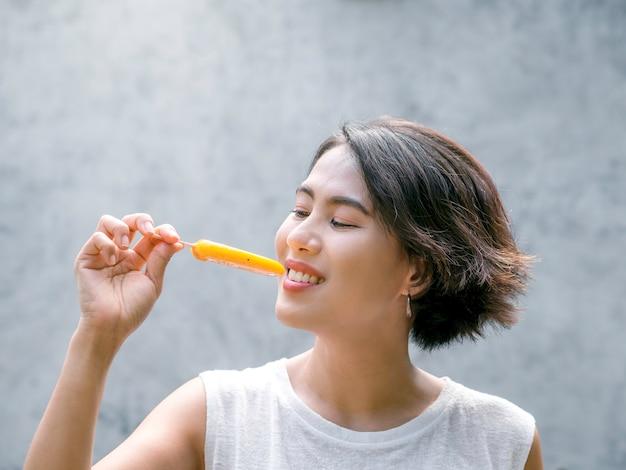 Vrouw die ijslollys eet. gelukkige mooie aziatische vrouw die een toevallig wit mouwloos overhemd draagt dat gele ijslolly houdt, in openlucht. glimlachend vrouwtje genieten van ijslolly in de zomer.