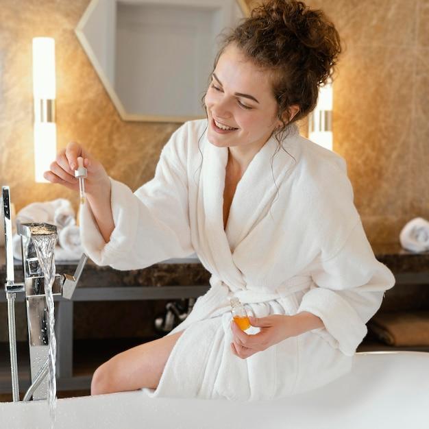 Vrouw die in badjas badkuip voorbereidt