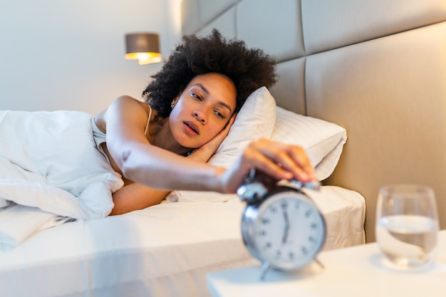 Vrouw die in bed ligt die een wekker in de ochtend om 7 uur uitzet.
