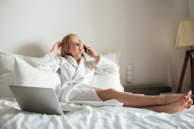 Vrouw die in bed ligt en op mobiele telefoon spreekt