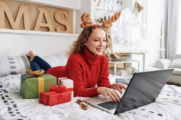 Vrouw die in bed op kerstmis werkt