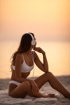 Vrouw die in bikini van muziek met hoofdtelefoons op aard genieten