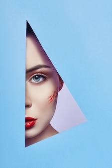 Vrouw die in blauw driehoeksgat kijkt