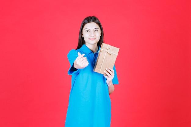 Vrouw die in blauw overhemd een kartonnen minigiftdoos houdt en vingerhartgebaar doet