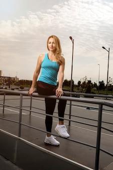Vrouw die in blauwe en zwarte fitnessuitrustingen vandaar op metaal zit.