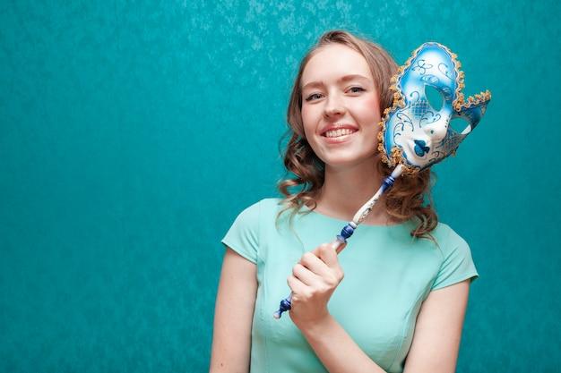 Vrouw die in blauwe kleding een carnaval-masker houdt