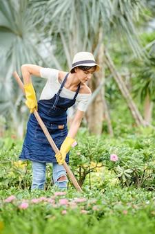 Vrouw die in bloementuin werkt