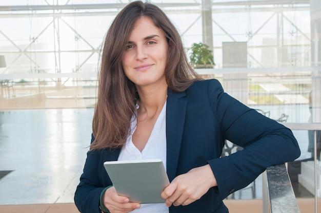 Vrouw die in bureau camera bekijkt, die tablet in handen houdt