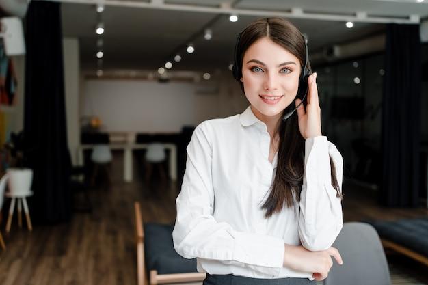 Vrouw die in call centre met hoofdtelefoon werkt die telefoongesprekken beantwoordt