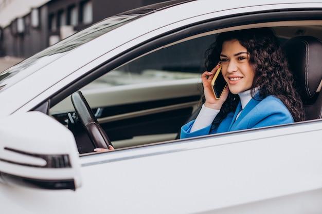 Vrouw die in de auto zit en mobiele telefoon gebruikt