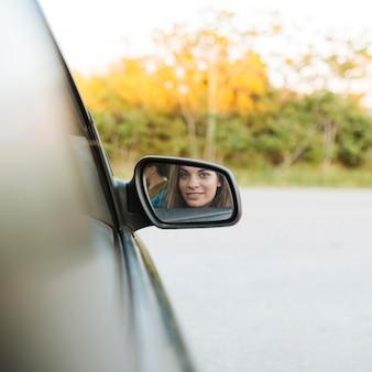 Vrouw die in de autospiegel kijkt terwijl het zijn in de auto